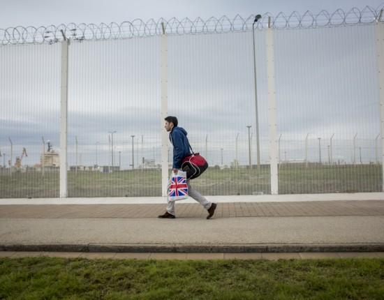 Un réfugié passe devant une barrière anti intrusion qui borde la zone portuaire de Calais.