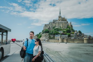 23 juin 2015 : Un jeune couple se prend en photo devant le Mont Saint-Michel avec une perche à selfie. Le Mont Saint-Michel (50), France June 2015: A young couple takes pictures in front of the Mont Saint-Michel with a Selfie stick.