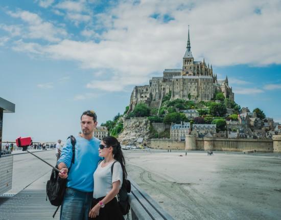 23 juin 2015 : Un jeune couple se prend en photo devant le Mont Saint-Michel avec une perche à selfie. Le Mont Saint-Michel (50), France  June 2015: A young couple takes pictures in front of the Mont Saint-Michel with a Selfie stick.