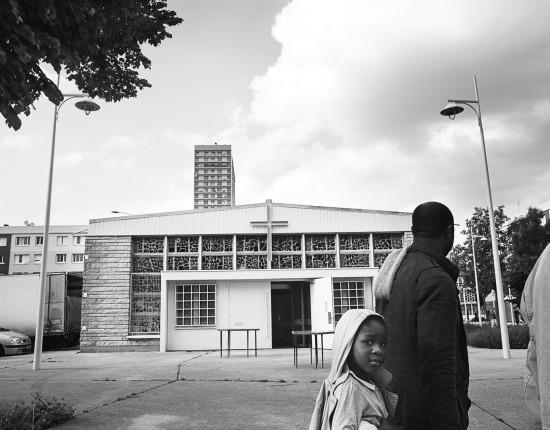 25 mai 2016 : Des habitants de la cité des Quatre Mille passent devantla chapelle de l'Emmanuel qui vient d'être rénovée. Le chantier a été réalisé par des associations d'insertion. Au fil des années, la petite chapelle cinquantenaire est devenue un lieu de rassemblement multiculturel où des croyants de toutes confessions peuventvenir s'y recueillir. La Courneuve (93), France.