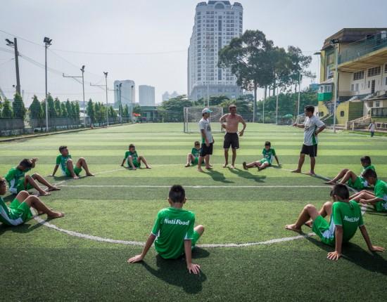 7 décembre 2015 : Les 10 recrues de la nouvelle académie JMG font le point sur leur entrainement du matin avec leur entraineur Franck Durix (au centre, torse nu). Les entrainement ont lieu 2 fois par jour, le matin et en fin d'après-midi. A 8h du matin, il fait déjà plus de 30°C. Hô Chi Minh-Ville, Vietnam.                                  December 7, 2015 : The 10 recruits of the new JMG  academy an update on their morning training with their coach Franck Durix (center shirtless ) . The training takes place 2 times a day, morning and late afternoon. At 8am, it is already over 30 ° C. Ho Chi Minh City, Vietnam.